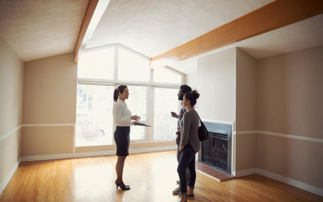 woman showing buyers a house