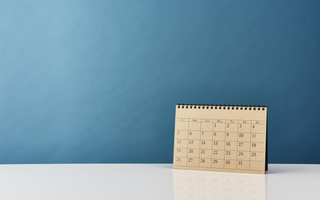 paper calendar standing upright against blue background