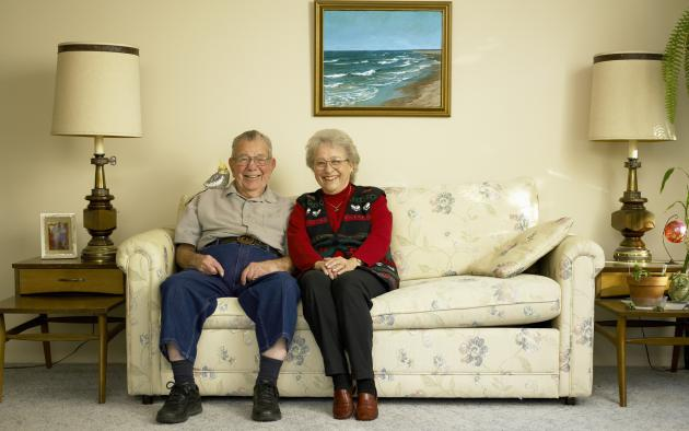 Older couple sitting on couch smiling