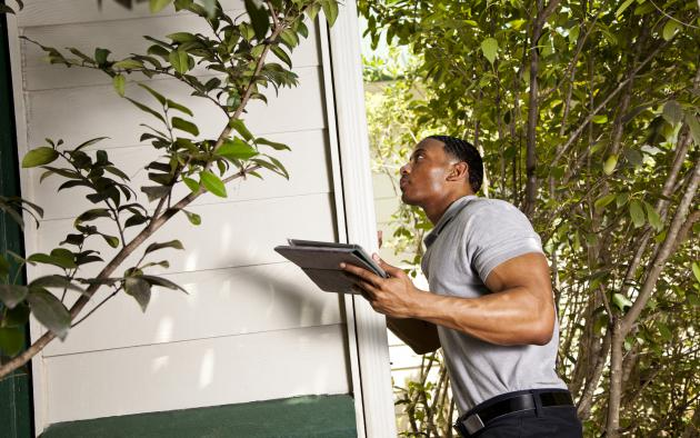 Inspector with clipboard inspection a home's exterior