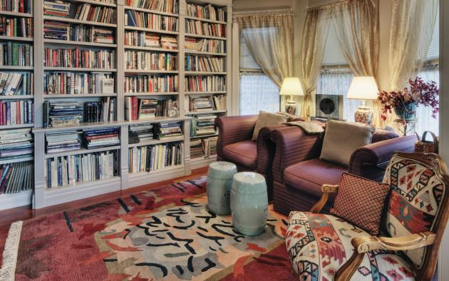 cozy living room with 3 armchairs and full bookcase wall
