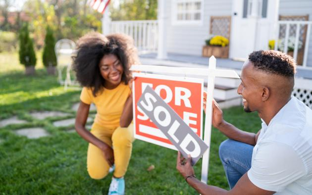 Husband and wife showing off sold sign in front of house