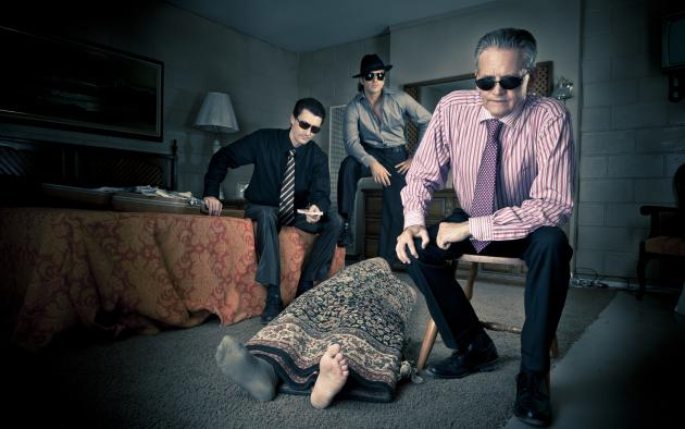 3 gangsters relax near body rolled up in a carpet