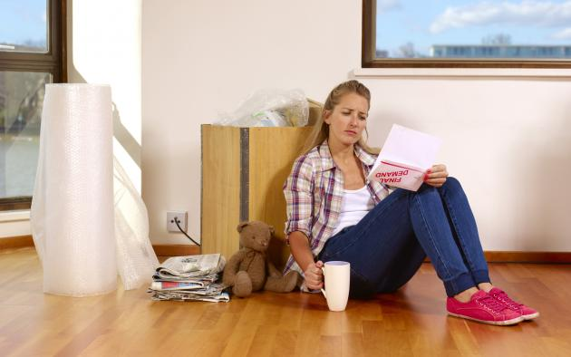 Unhappy female renter sits on the floor with a demand letter in her hand