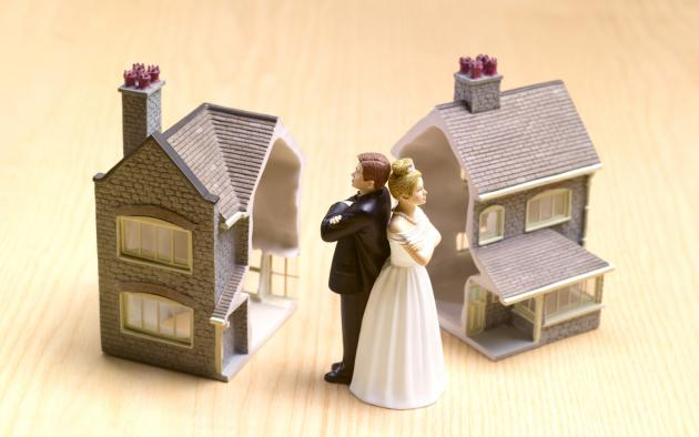 Cake topper couple back to back with two toy homes in background