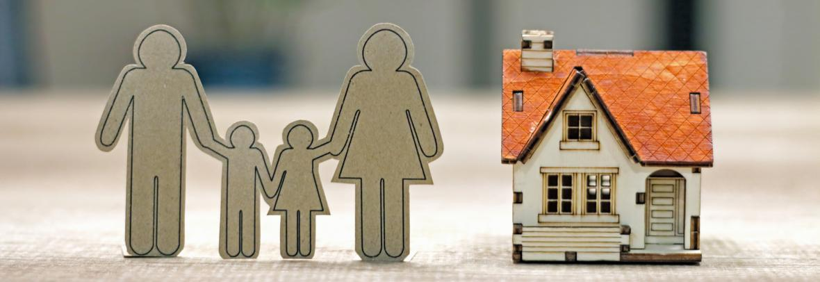 Sustainable financial goal for family life concept. Family Paper and house model on the table