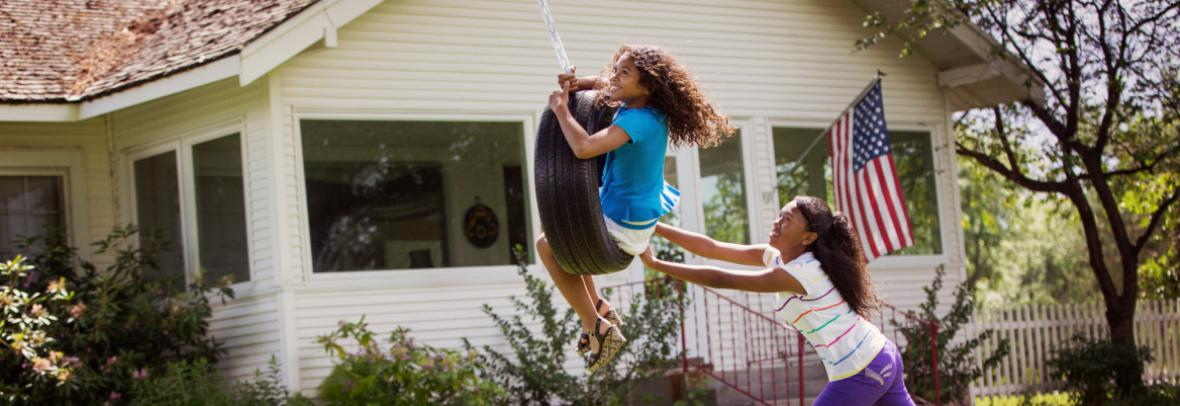 Kids playing on tire swing in front yard of house