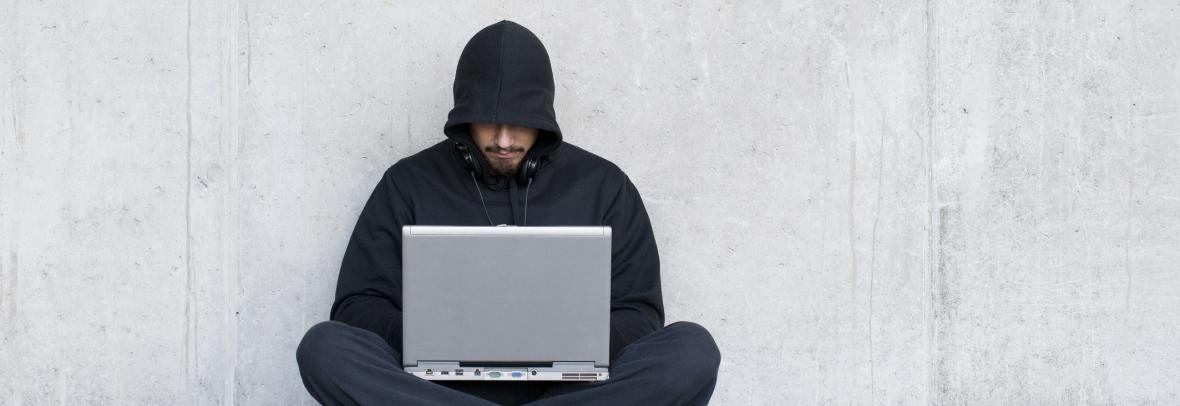 man in hood using computer