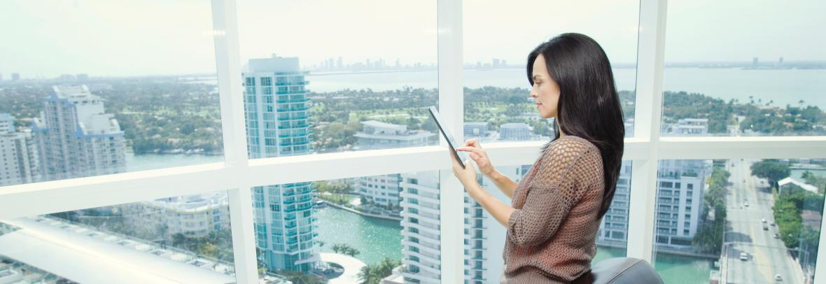 Woman with tablet in office overlooking city skyline