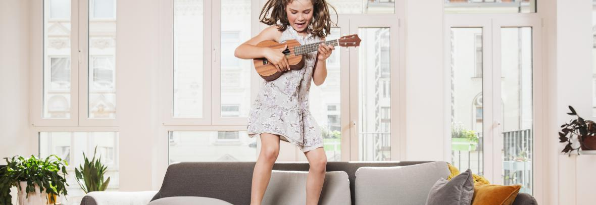 girl with ukelele jumping on couch