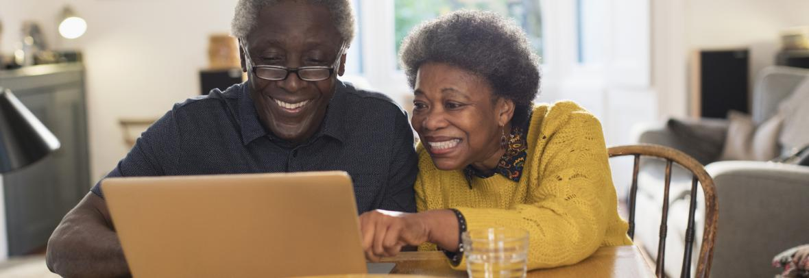 older couple looking at computer and smiling