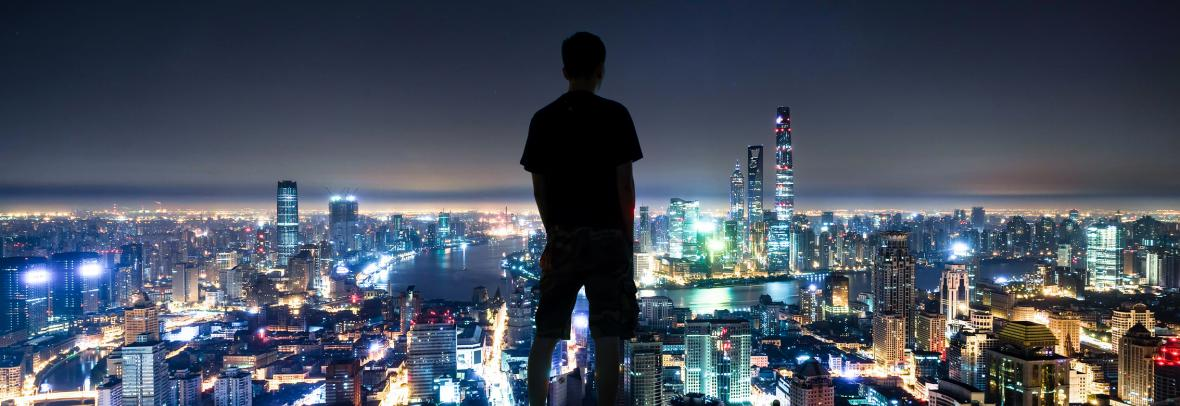 Man looking at nighttime skyline of Shanghai
