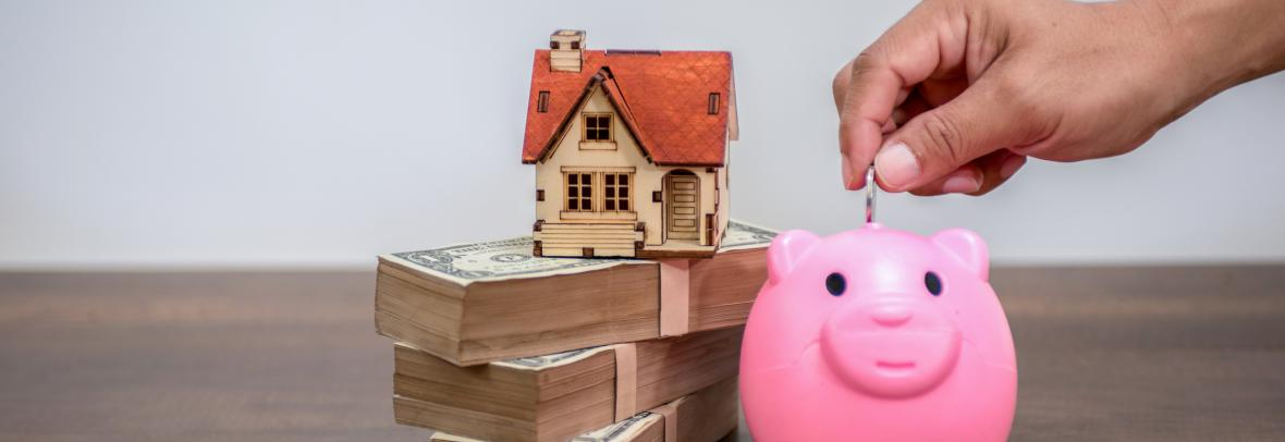 Toy home on top of money beside a piggy bank