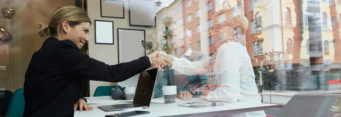 Woman shaking hands with image of another woman in the window