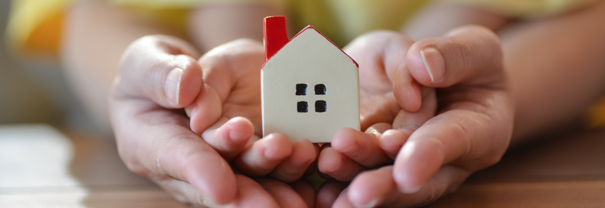 And adult and child's hands holding tiny house