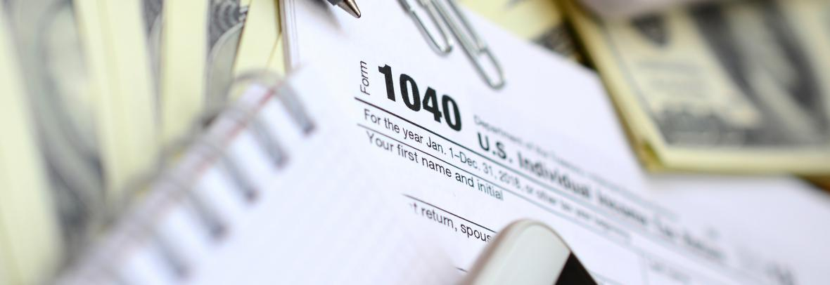 Tax form 1040 surrounded by paper and pens