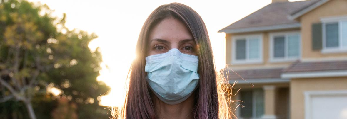 woman wearing face mask outside a house