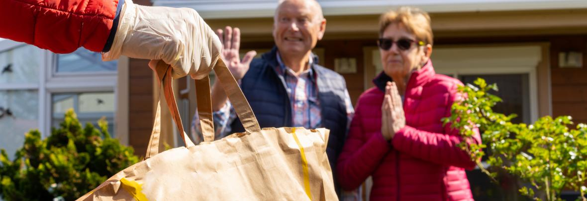 Gloved hand holding grocery bag delivered to thankful older couple