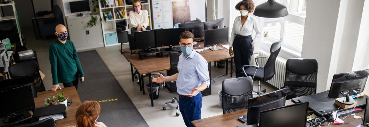 Co-workers social distancing and wearing masks in office