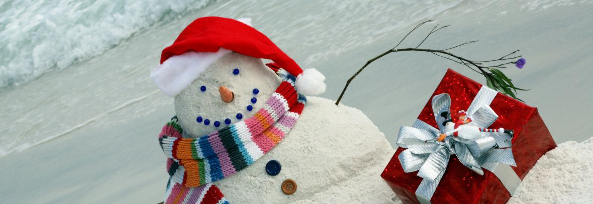 Snowman made of sand on the beach has a scarf and hat and Christmas gifts