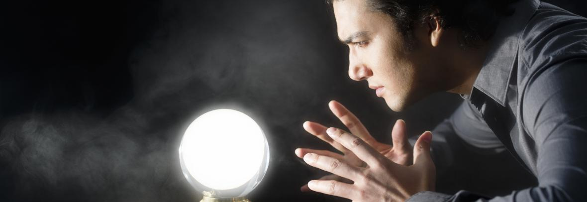 Man stares into a glowing crystal ball