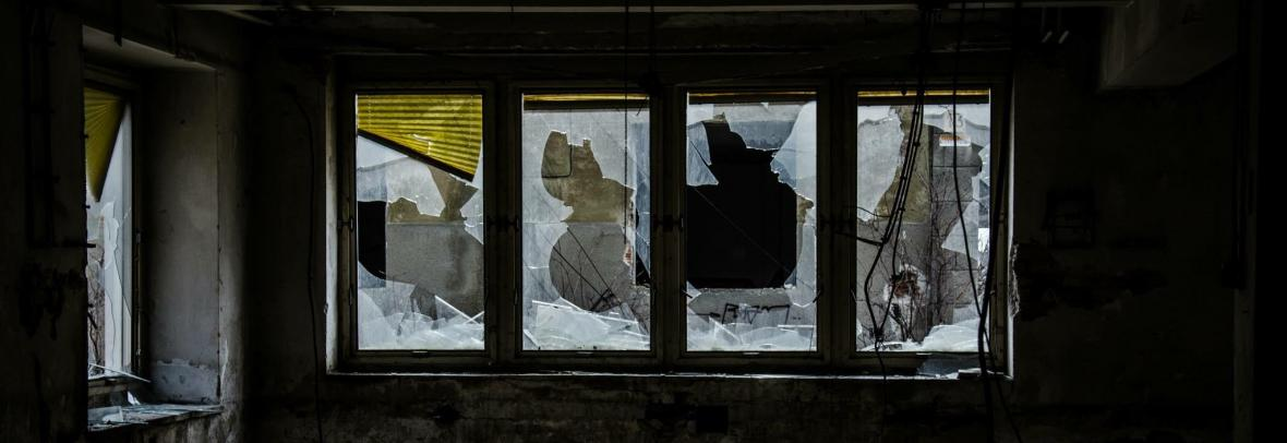 A row of broken windows and trash on the floor inside a fixer-upper