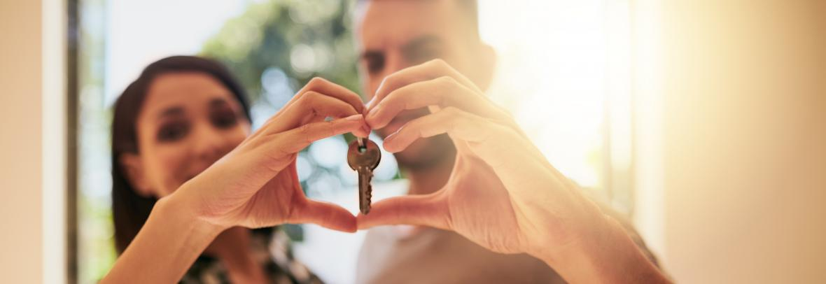 Portrait of a young couple holding the keys to their new home
