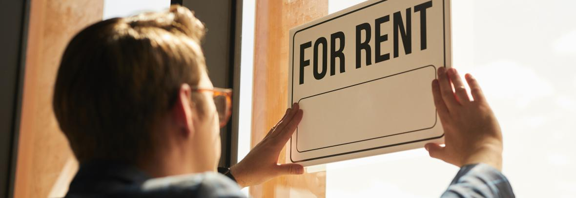Many hangs a for-rent sign in his window