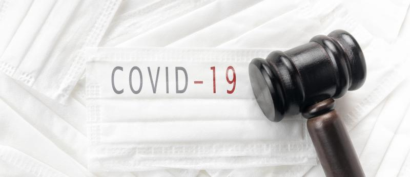 judge's gavel on top of masks that say COVID-19